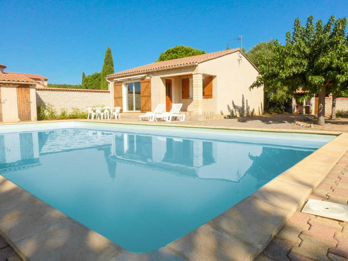 Maison piscine bleue terrasse et transats